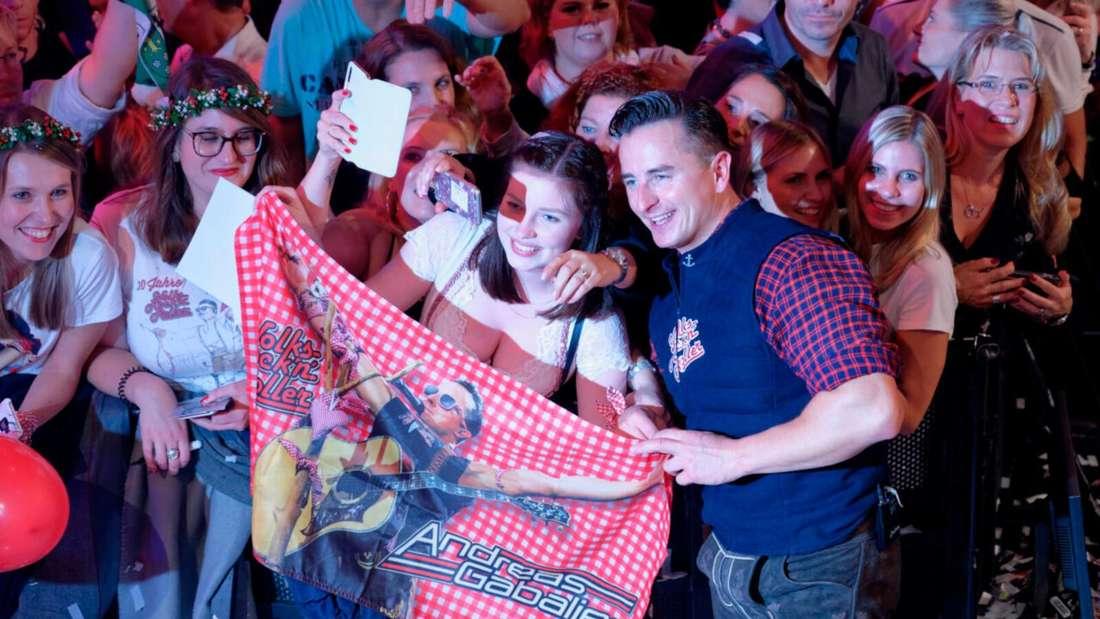 Andreas Gabalier lässt sich mit einem Fan fotografieren
