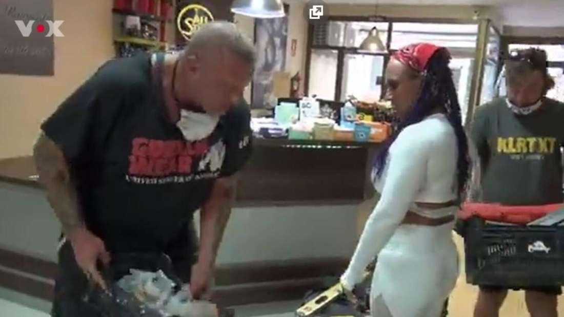 Caro steht im weißen Sport-Outfit auf der Bausstelle, neben ihr Andreas, der Utensilien in der Hand hält