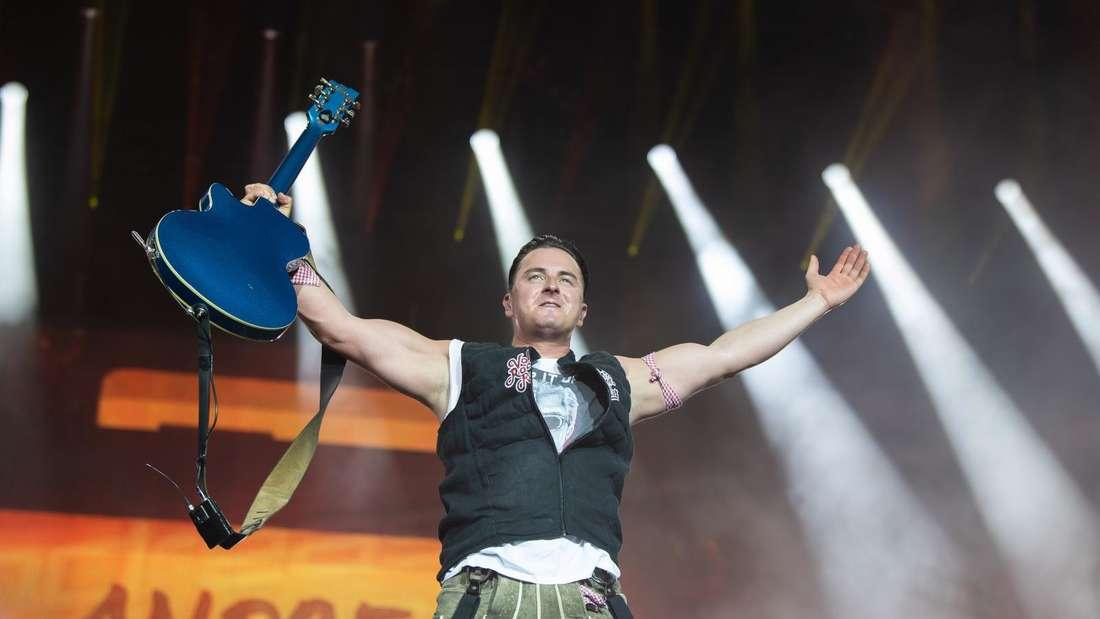 Andreas Gabalier steht auf der Bühne bei einem Konzert und reißt die Arme hoch