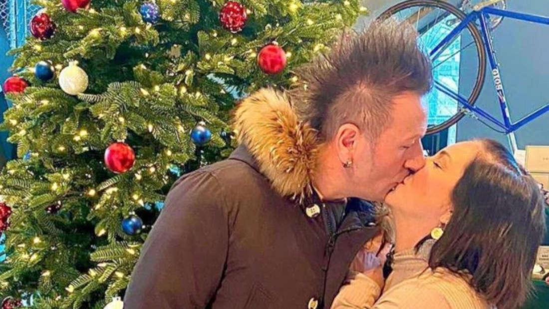 Daniela Büchner und Ennesto Monte küssen sich vor einem Weihnachtsbaum