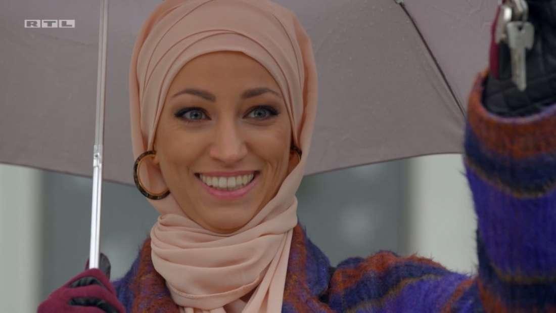 Nazan steht mit einem Regenschirm auf der Straße