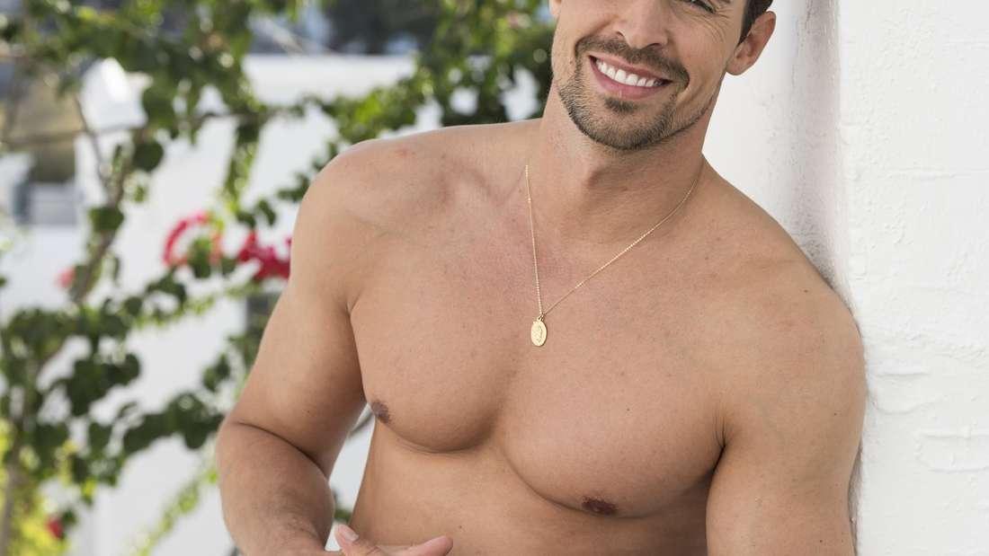 Dario posiert mit einer schwarzen Badehose an einer weißen Hauswand