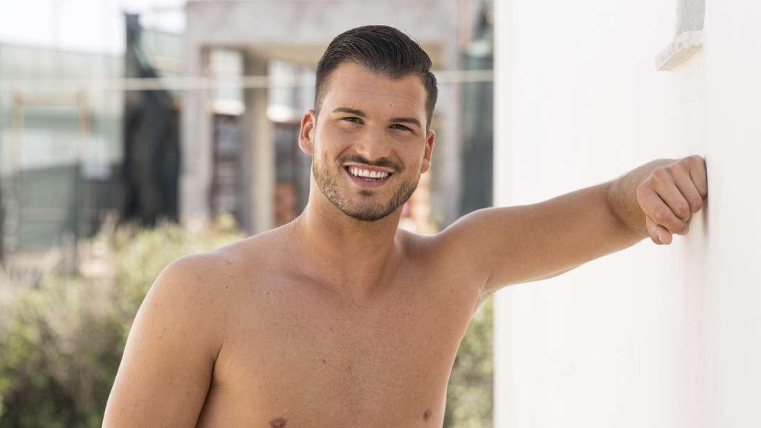 Marko posiert mit einer orangen Badeshorts vor einer weißen Wand