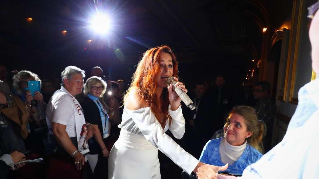 Andrea Berg gibt bei einem Konzert, während des Singens, einem Fan die Hand