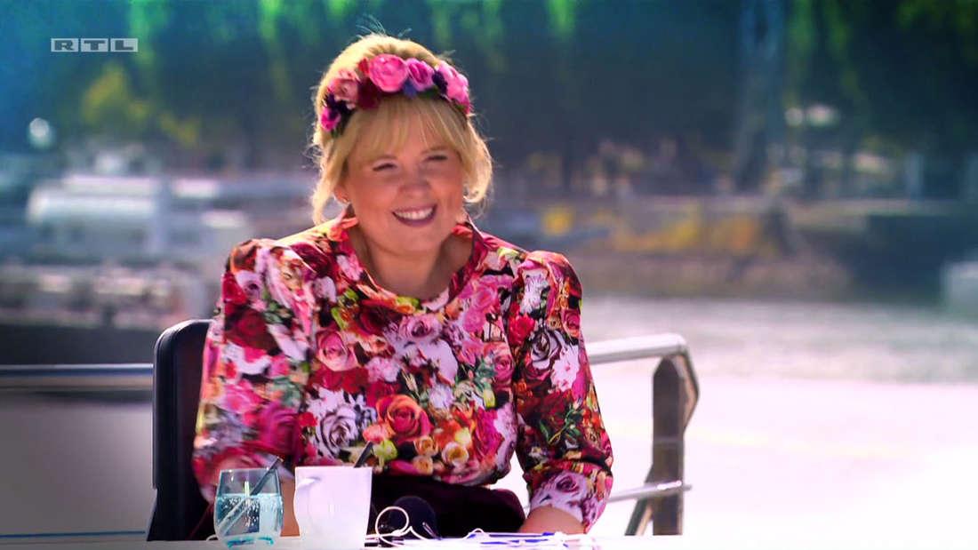 Maite Kelly sitzt am Jurypult. Sie trägt eine geblümte Bluse und einen Blumenreif in den Haaren
