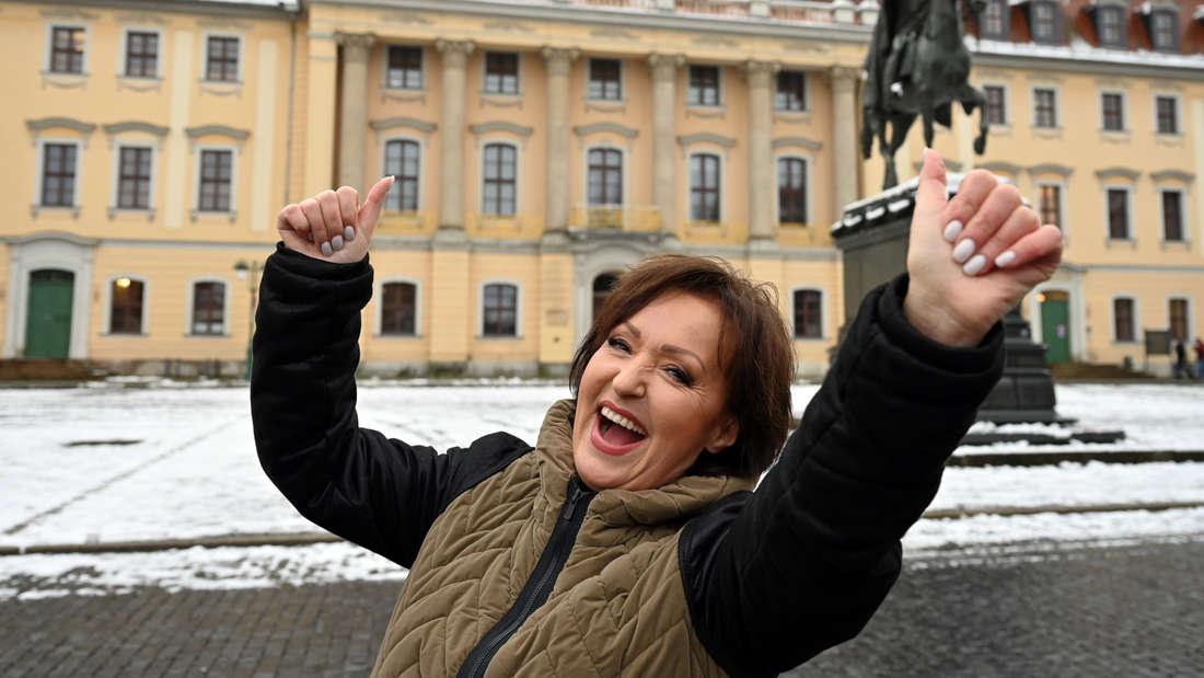 Ute Freudenberg lacht und reißt die Arme nach oben und ist vor einem Gebäude im Winter
