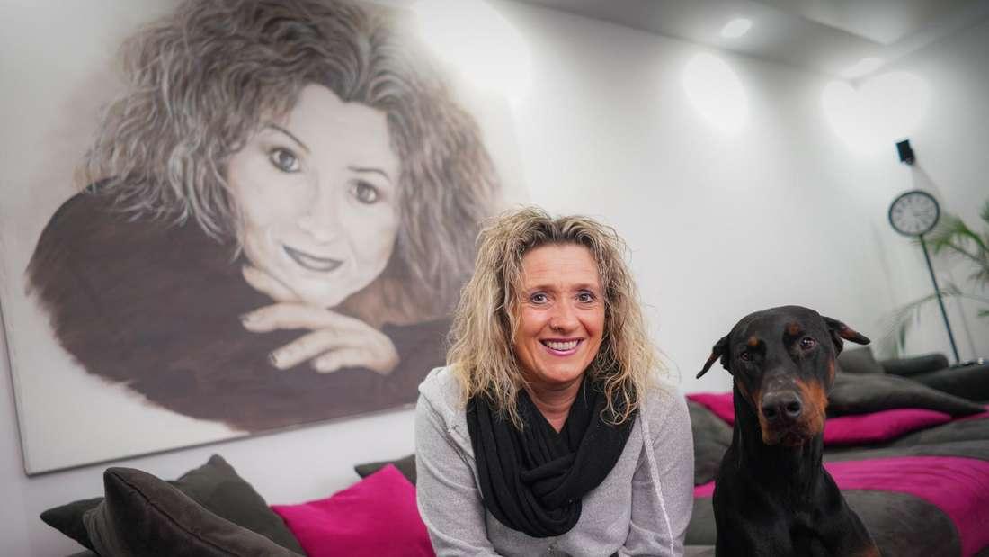Daniela Alfinito sitzt auf dem Sofa, neben ihr ein Hund
