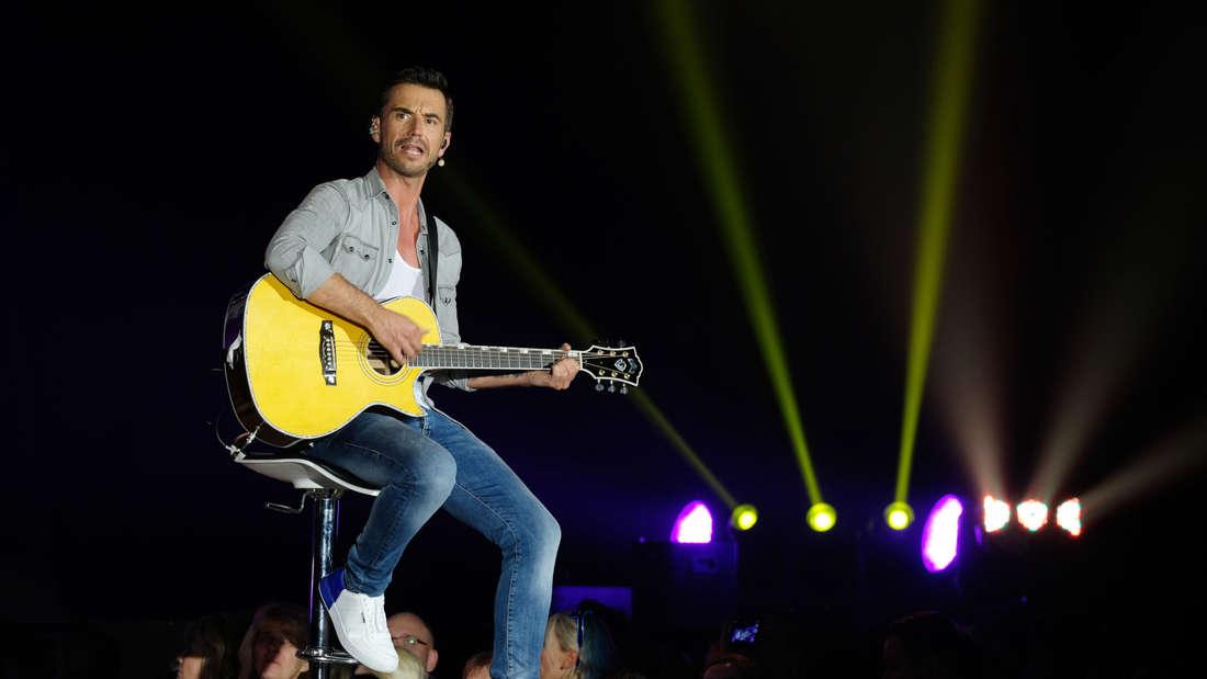 Florian Silbereisen sitzt auf der Bühne mit einer Gitarre und singt