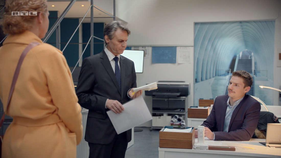 Moritz sitzt am Schreibtisch, Jo Gerner daneben hält das Geldbündel in der Hand, Nina hat den Rücken zur Kamera
