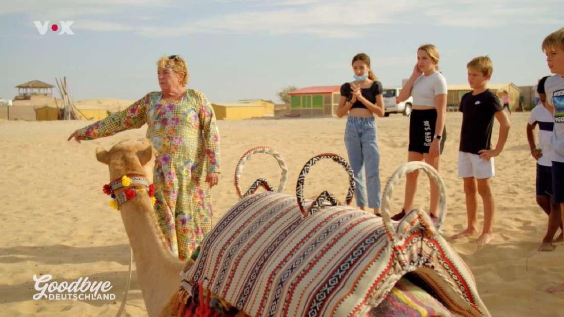 Kamel-Uschi steht mit Kindern neben einem sitzenden Kamel in der Wüste.