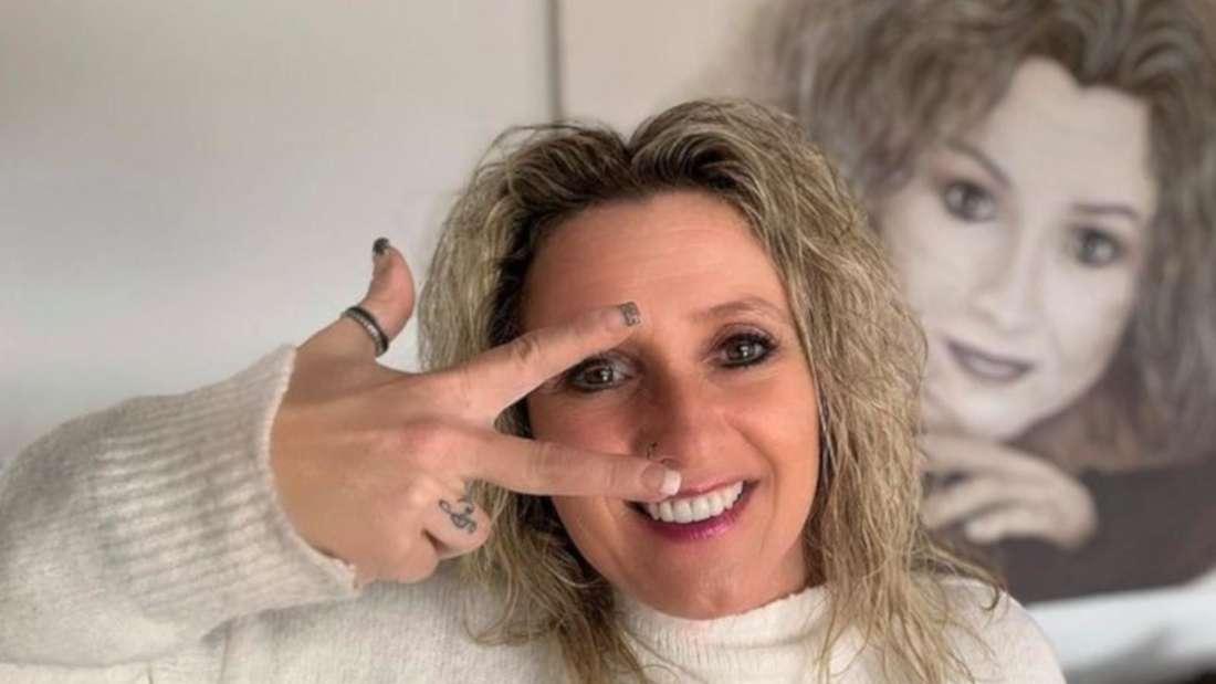 Daniela Alfinito formt eine drei mit ihrer Hand und lächelt