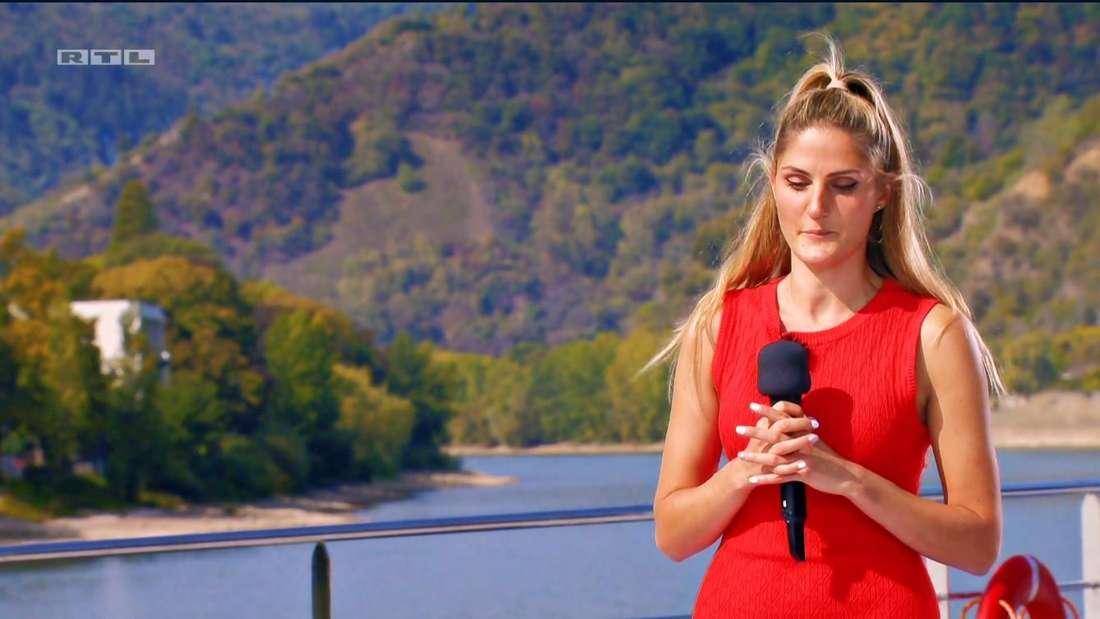 Nadine in einem roten Kleid, mit einem Mikrophon in der Hand