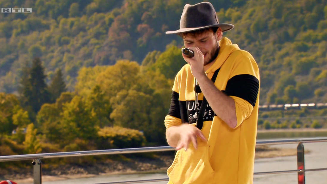 Marc Wasserburg rappt, er hält ein Mikrophon in der Hand