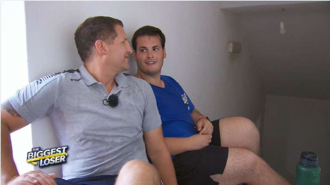 Gianluca und Ramin Abtin sitzen nebeneinander auf dem Boden. Gianluca strahlt den Coach an