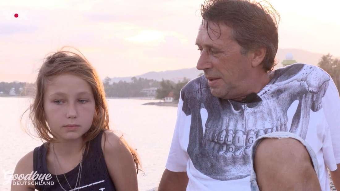 Frank sitzt gemeinsam mit seiner Tochter am Meer