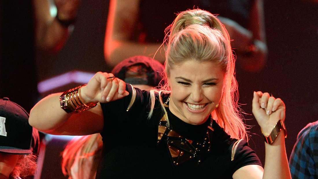 Beatrice Egli lacht und tanzt auf der Bühne.