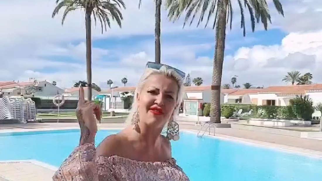 Ginger Costello-Wollersheim in einem gliternden Jumpsuir vor einem Pool