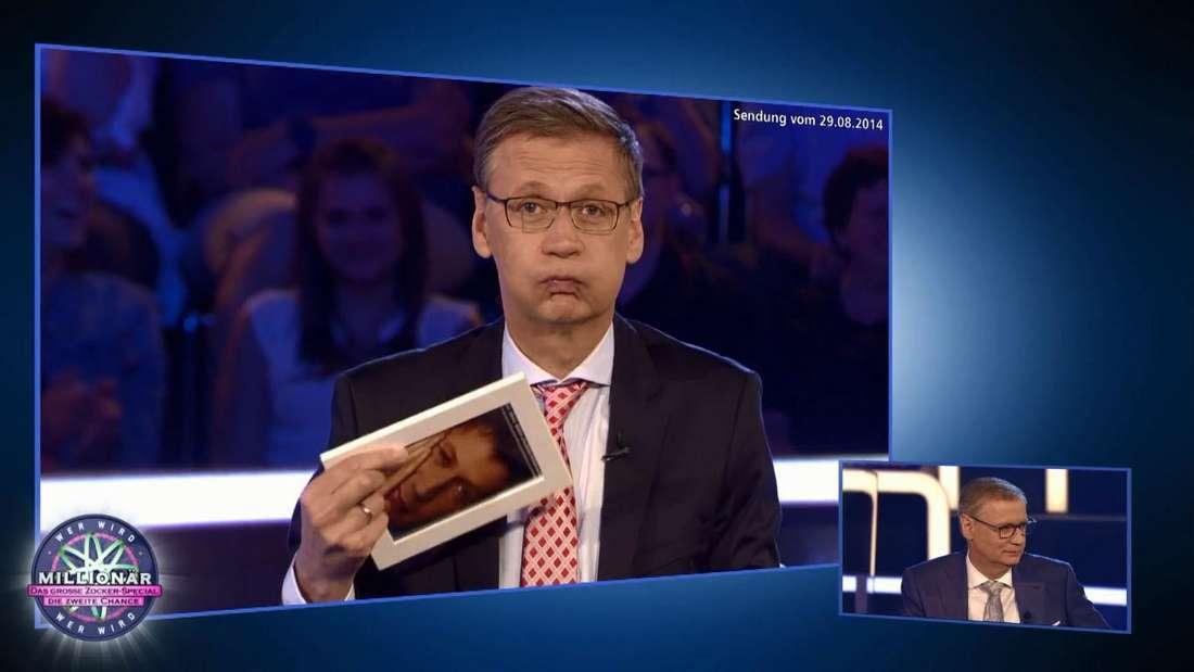 Wer wird Millionär: Rückblick auf 2014 mit Günther Jauch, der ein Bild in der Hand hält und die Backen aufbläst