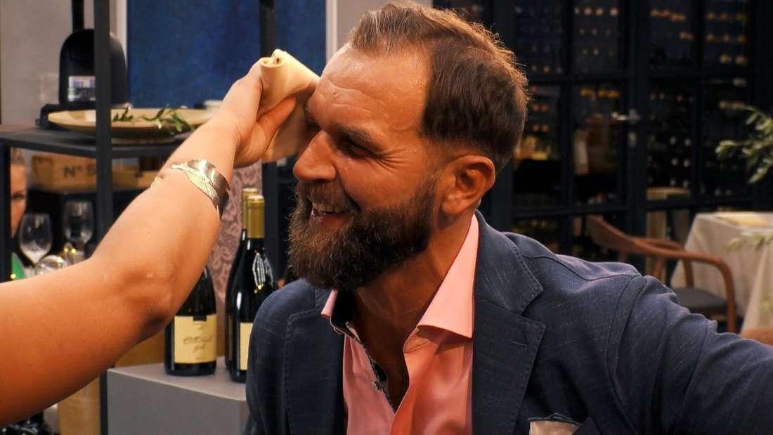 Adams Date-Partnerin tupft mit einem Tuch den Schweiß von Adams Stirn ab