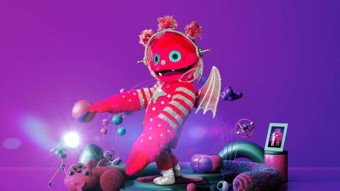 Der Monstronaut ist pink und flauschig, im Hintergrund sind verschiedene Gegenstände, wie Planeten und eine Lampe