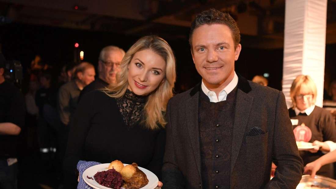 Anna-Carina Woitschack und Stefan Mross halten zwei gefüllte Teller in die Kamera