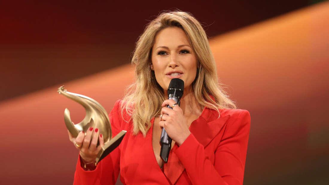 """Helene Fischer steht in einem roten Abendkleid mit der Auszeichnung der """"Goldenen Henne"""" auf der Bühne und spricht in ein Mikrofon."""