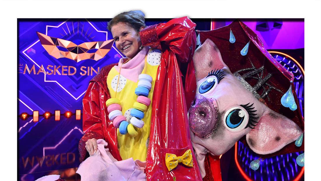 Katrin Müller-Hohenstein lächelt, im Hintergrund die Schwein-Maske vom Kostüm (Fotomontage)