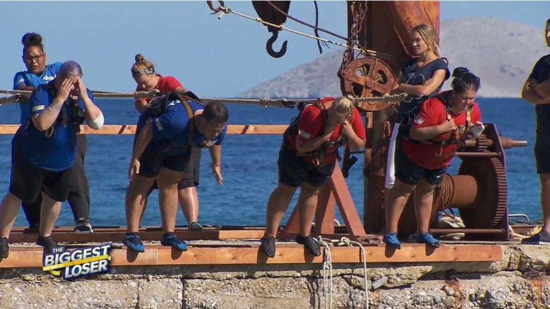 Die Kandidaten hängen an Seilen nach vorne. Gianluca streckt den Po raus, alle anderen bilden mit ihren Körpern eine Gerade
