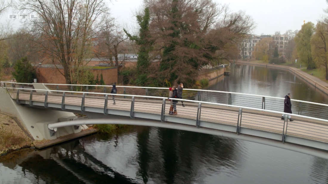 Thaddäus Meilinger seine Frau Fritzi stehen auf einer Brücke im Park und küssen sich