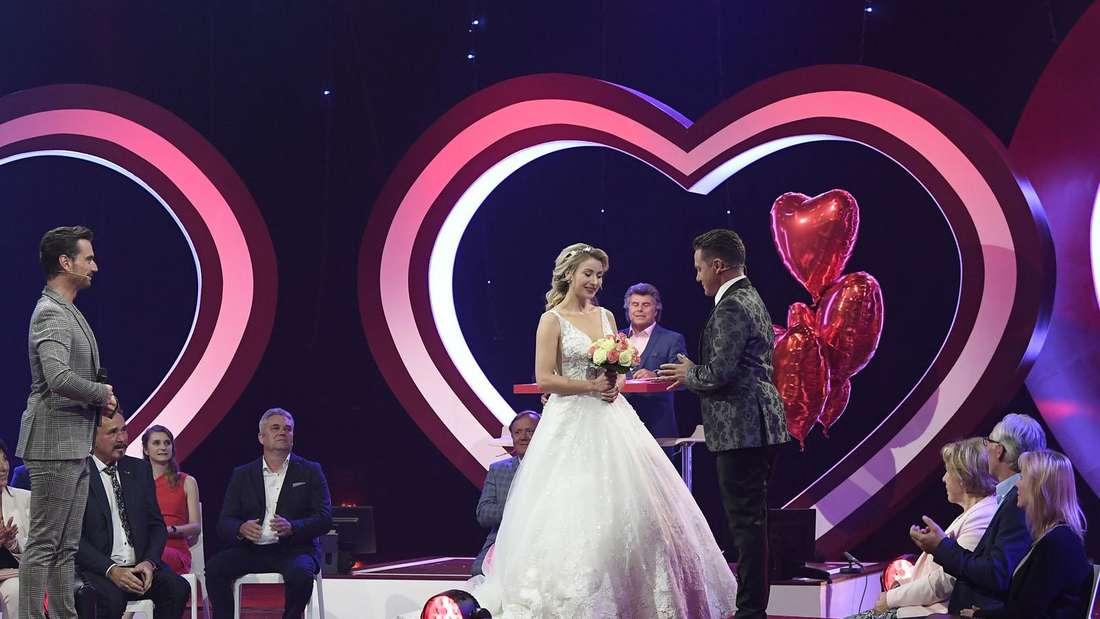 Auf der Bühne steht Anna-Carina Woitschack im weißen Hochzeitskleid, rechts neben ihr steht Stefan Mroos. Beide geben sich das Ja-Wort