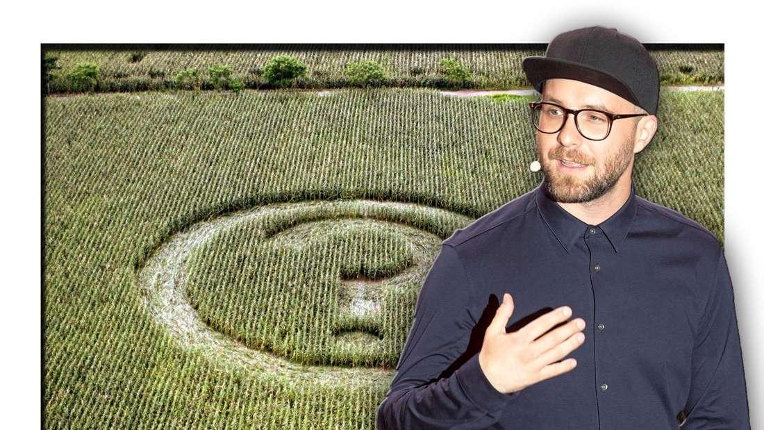 Popsänger Mark Forster steht vor einem Feld, in welchem ein Fragezeichen als Kornkreis zu sehen ist (Fotomontage)
