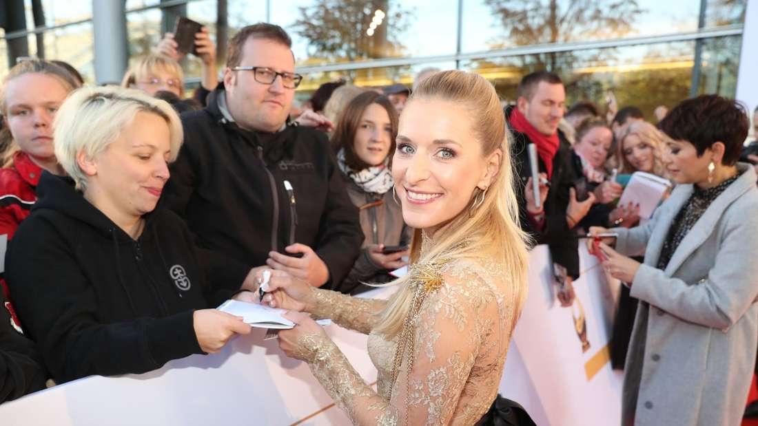 Stefanie Hertel steht auf dem roten Teppich und gibt Fans Autogramme