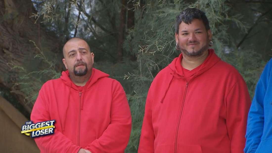 Benny und Toni haben beide ein rotes Sweatshirt an und schauen in die Kamera.
