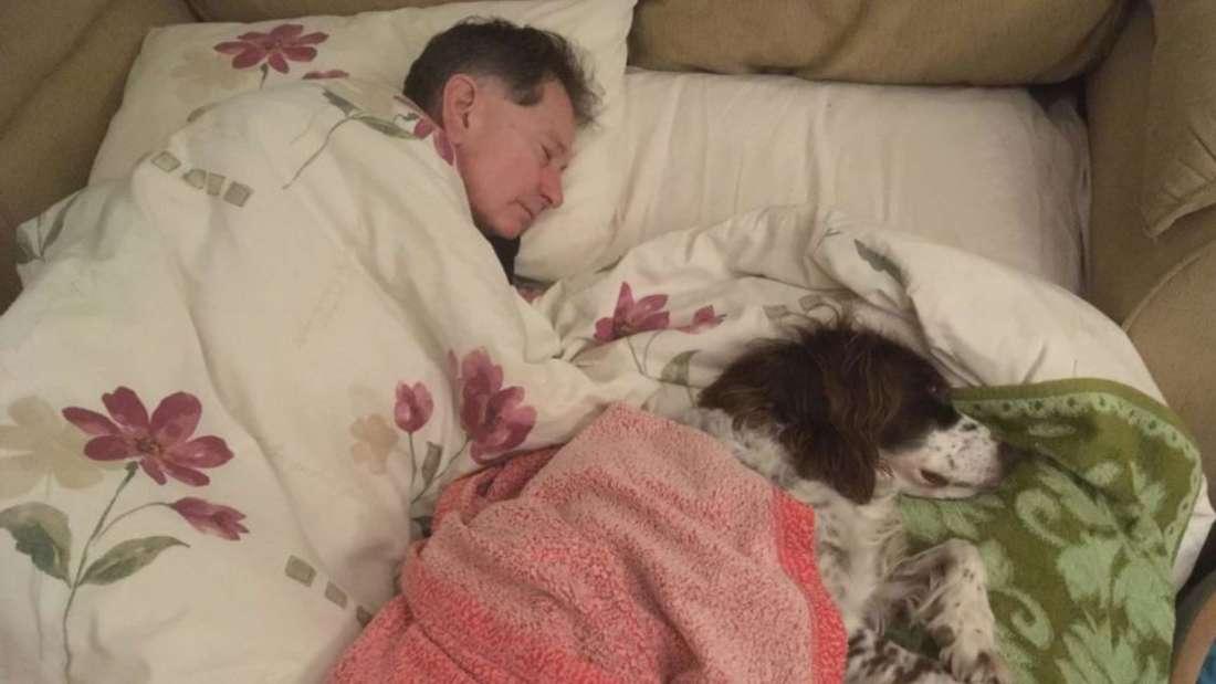 Ein Mann schläft neben einem Hund.