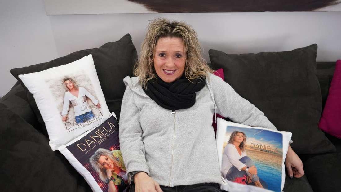 Daniela Alfinito sitzt auf einem Sofa, um sie herum Kissen mit ihrem Foto darauf.