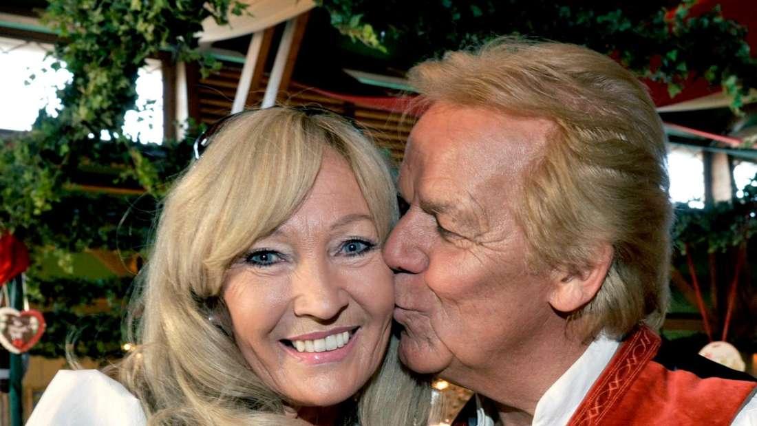 Mel und Judith sind in Tracht gekleidet, dabei gibt Mel seiner Frau einen Kuss.