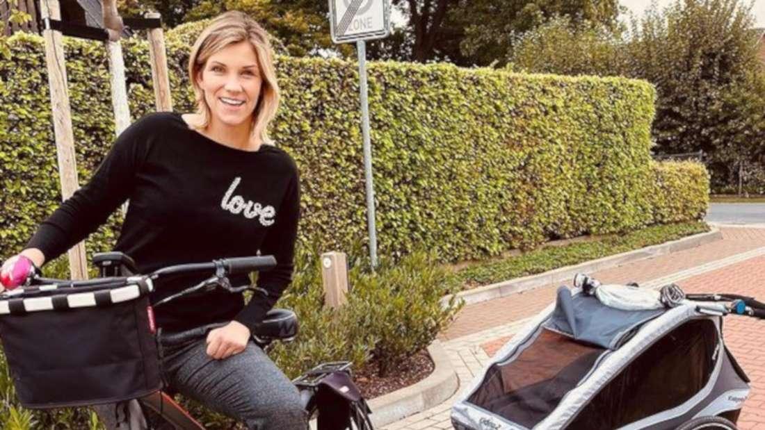 Anna-Maria Zimmermann auf einem Fahrrad mit Kinderanhänger