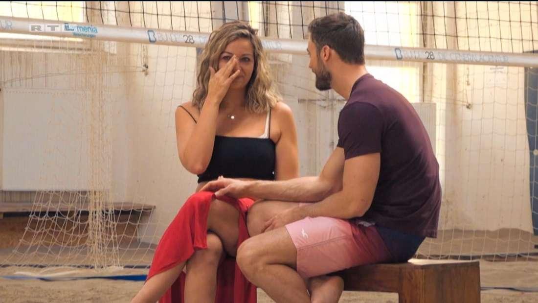 Hannah und Niko sitzen nebeneinander auf einer Bank, sie wischt sich Tränen weg