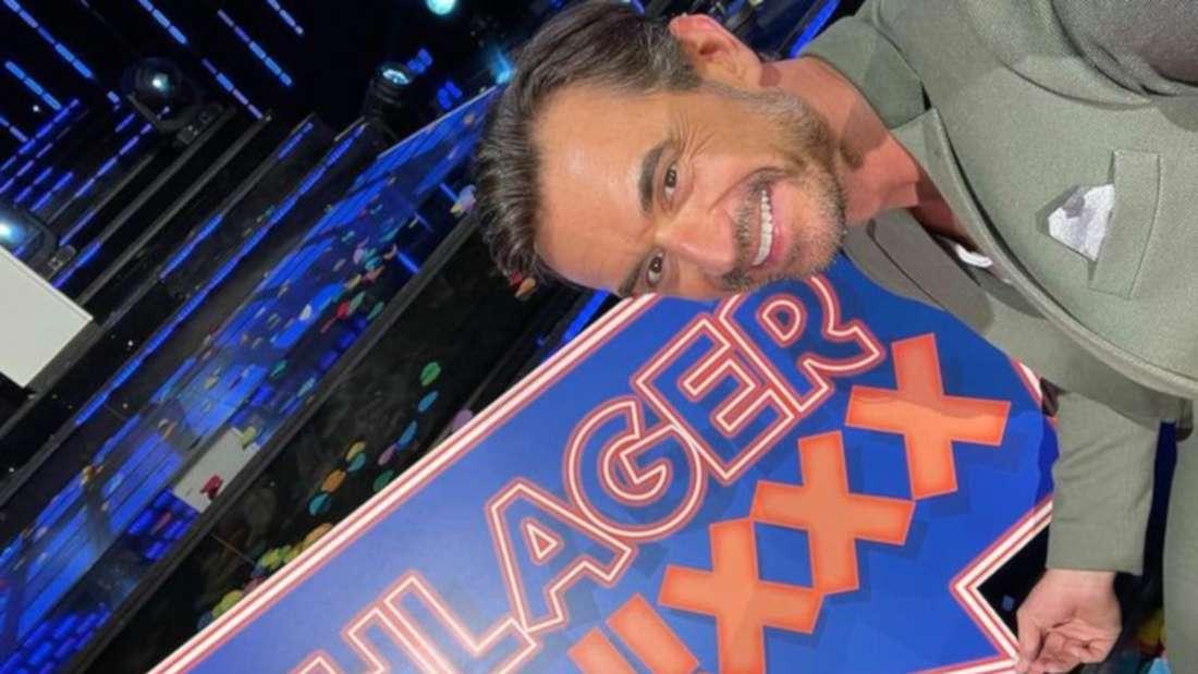 Florian Silbereisen zeigt lächelnd auf ein Schild mit dem Titel seiner TV-Show