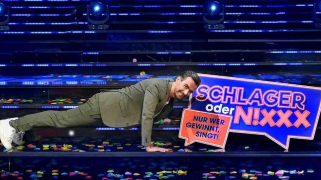 Florian Silbereisen macht neben einem Schild mit dem Titel seiner Show Liegestütze