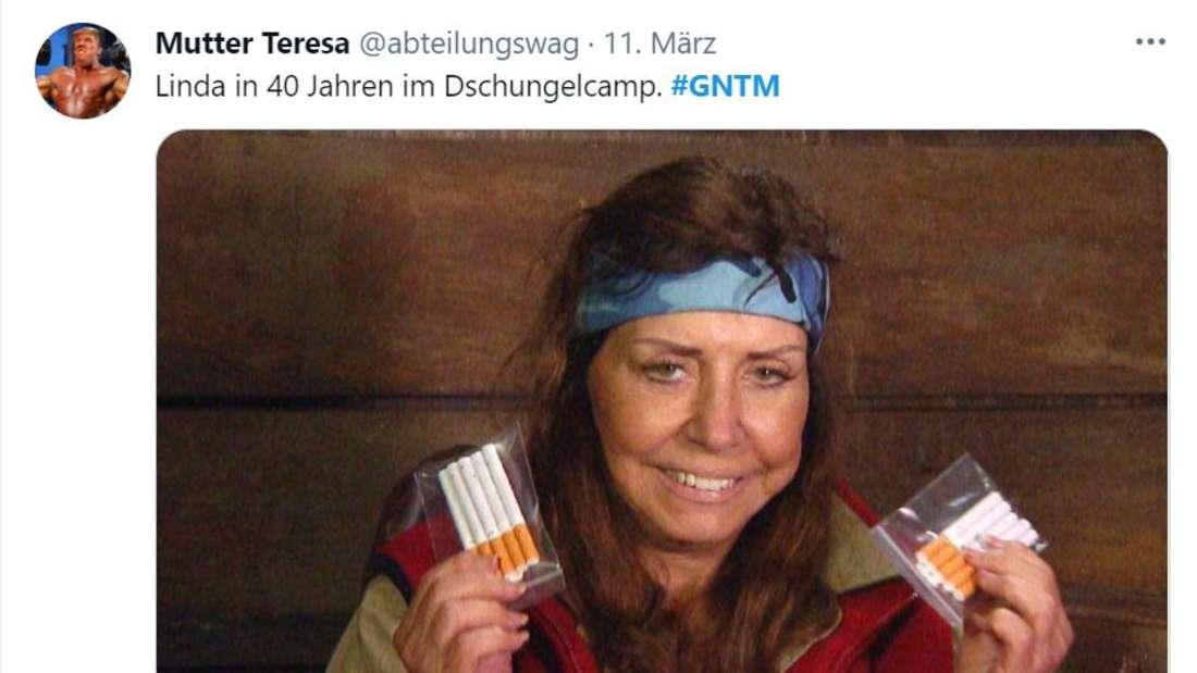 Eine Dschungelcamp-Teilnehmerin mit zwei Packungen Zigaretten in der Hand, sie sieht erschöpft aus, aber lächelt.