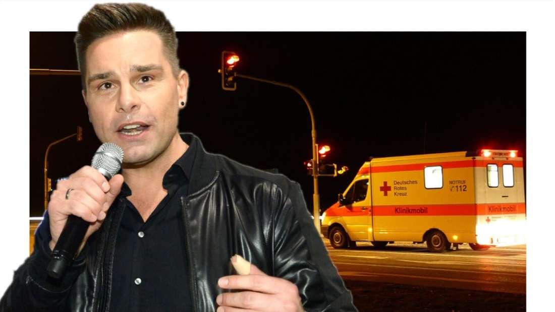 Eloy de Jong schaut ein wenig verzweifelt, ein Krankenwagen im Hintergrund (Fotomontage)