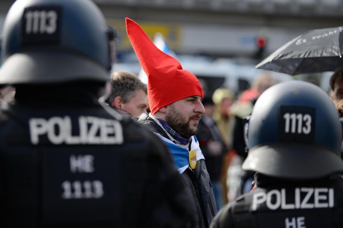 """Ein Teilnehmer mit einer roten Zipfelmütze und ohen Mund-Nasen-Bedeckung steht bei einer Kundgebung unter dem Motto """"Freie Bürger Kassel - Grundrechte und Demokratie"""" vor Polizisten."""