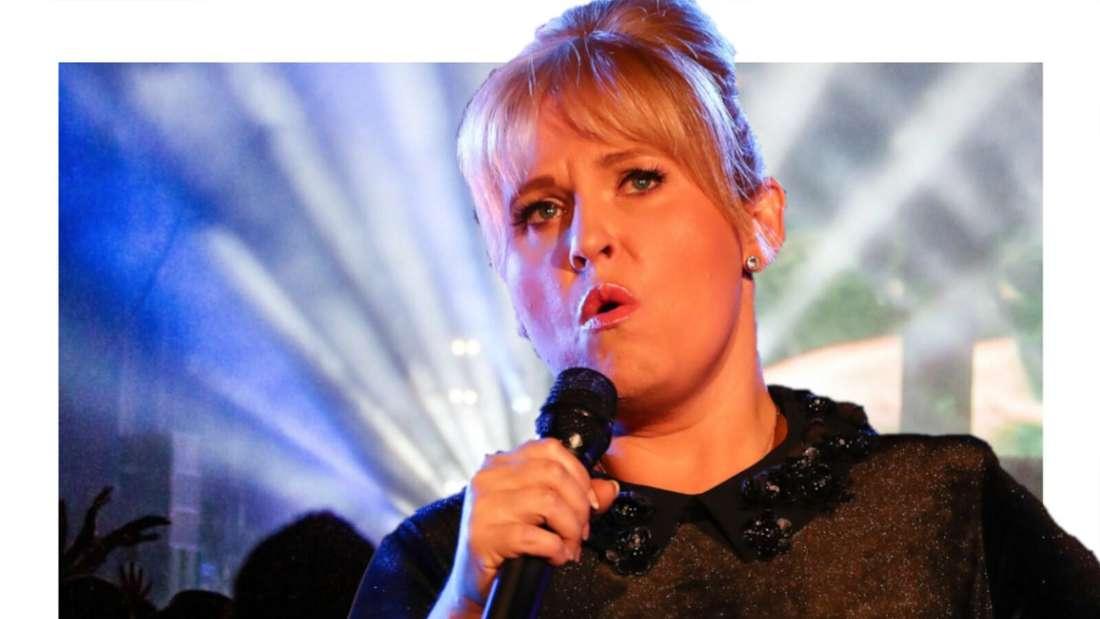 Maite Kelly schaut kritisch, im Hintergrund eine jubelnde Menge vor einer Bühne (Fotomontage)
