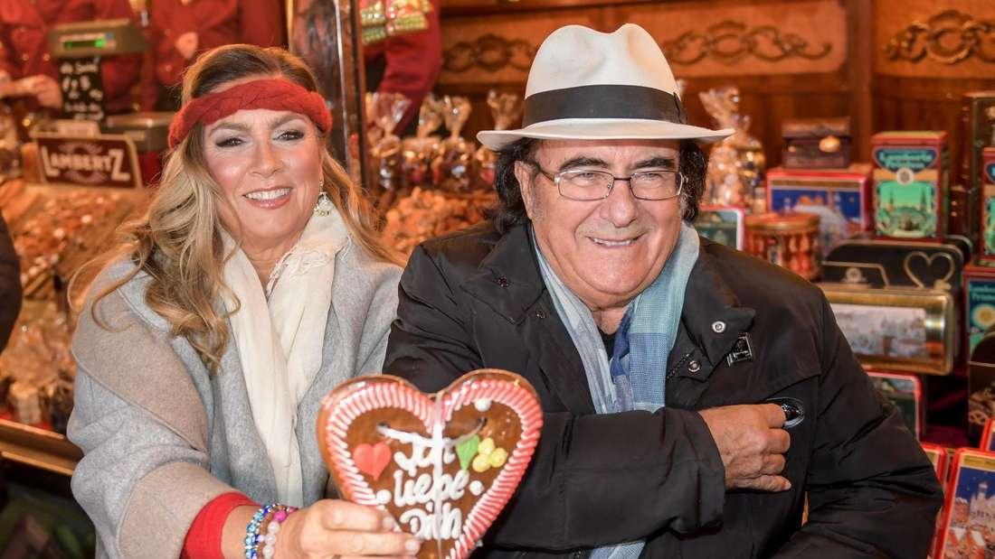 Al Bano & Romina Power bei ihrer Comeback-Tour. Das Paar lächelt und hält ein Lebkuchenherz hoch