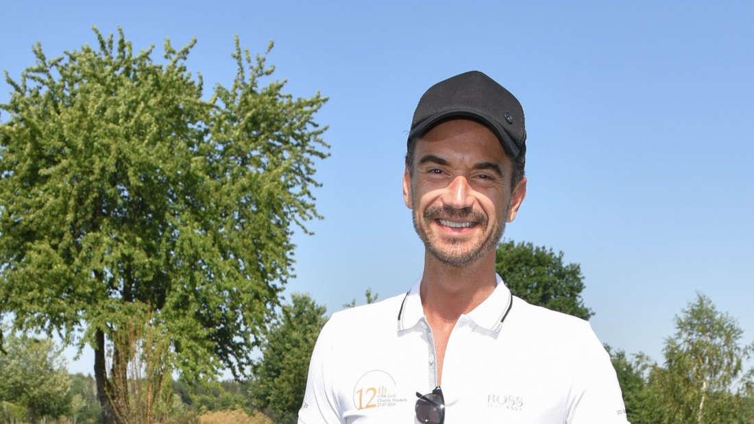 Florian Silbereisen bei Dreharbeiten für das Traumschiff. Der Schlagersänger steht in Afrika und lächelt in die Kamera.