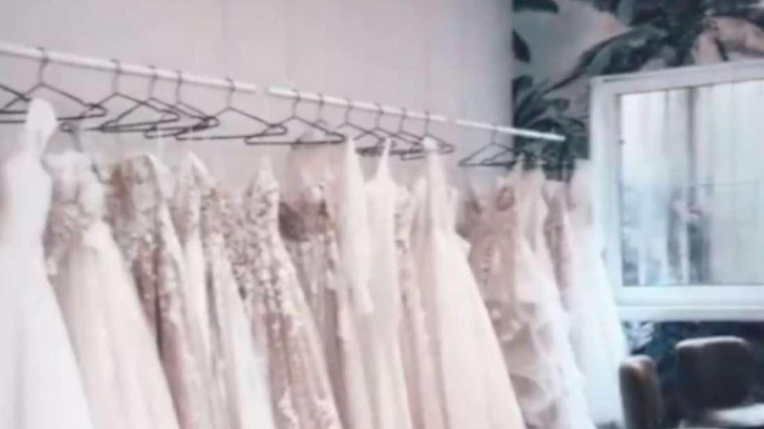 Mehrerer Hochzeitskleider hängen an einer Stange in einem Brautmode-Geschäft