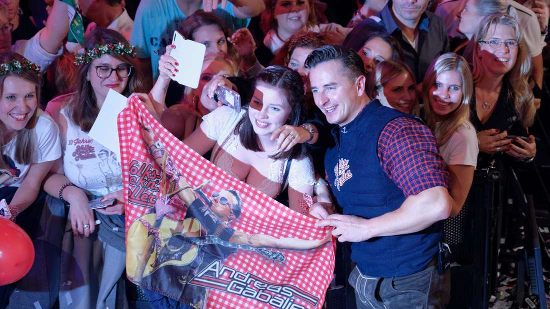 Andreas Gabalier zwischen einigen weiblichen Fans und hält dabei ein Tuch mit seinem Bild hoch