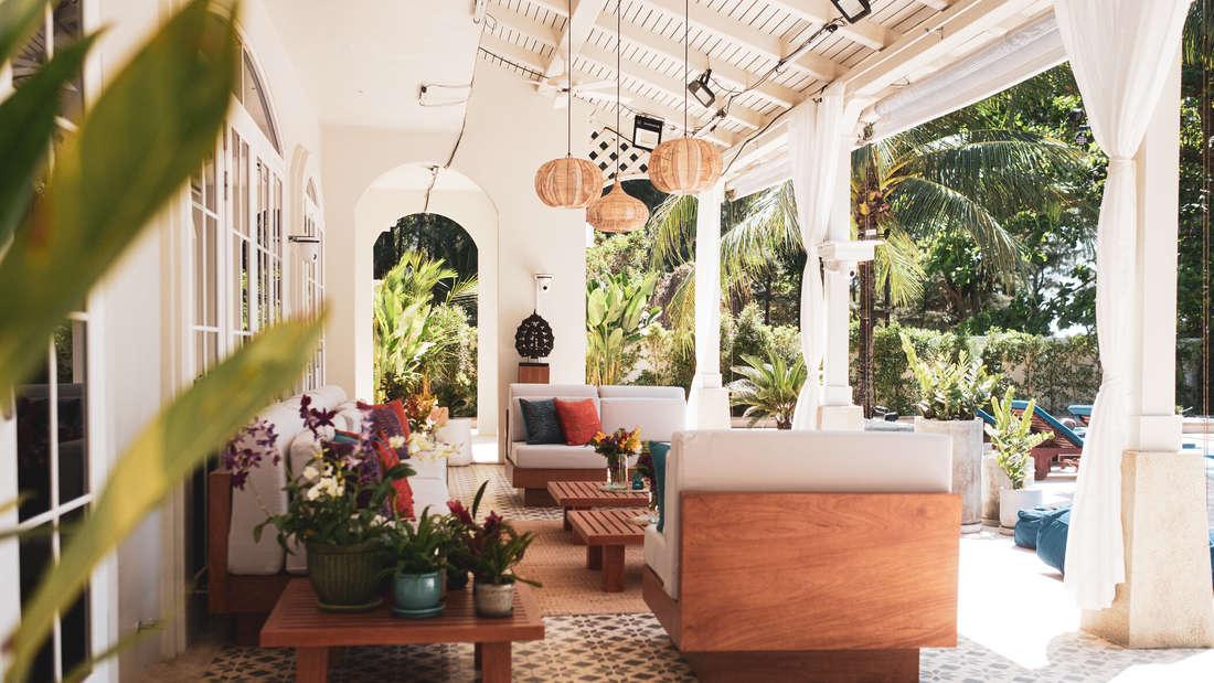 Terrasse mit Möbeln aus hellem Holz und weißen Polstern