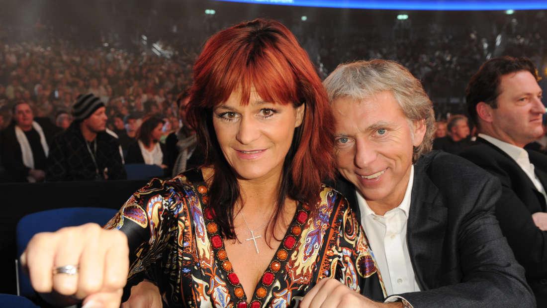 Andrea Berg und Uli Ferber sind zu Gast bei einem Boxkampf, ballen eine Faust und lächeln.